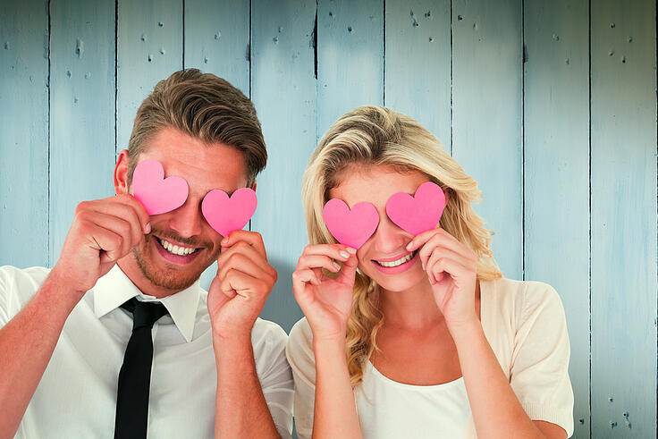 Attractive young couple holding pink hearts over eyes against wooden planks-1