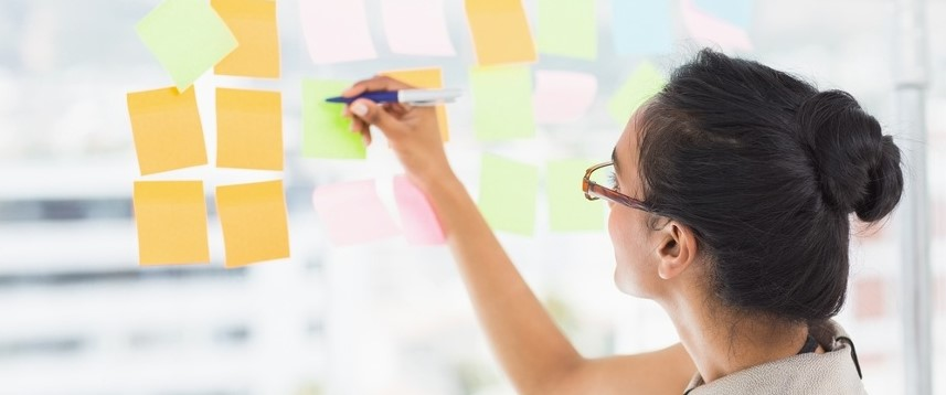 Smiling designer writing on sticky notes on window in creative office-1